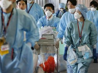 Quarantine officials at Narita Airport. Image (c) The Associated Press